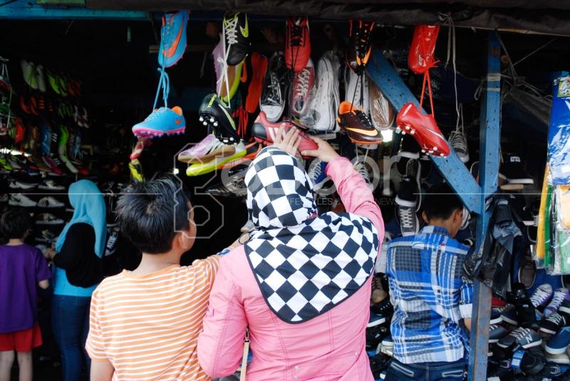 Seorang Ibu Sedang Memilih Sepatu Besersama Anaknya Di Pasar Poncol